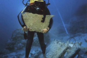 An archaeologist carrying an oxhide ingot to be raised to the surface. (Photo: INA) Slide# KW-4768.1.  REF628