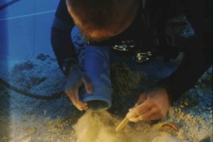 Archaeologist carefully removing sediment from ceramics (Photo: Don Frey) Slide # TEK-025. REF656