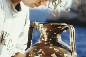 Assistant conservator Mehgan Ryan inspects a table amphora. (Photo: Don Frey). Slide # TEK-037.  REF648