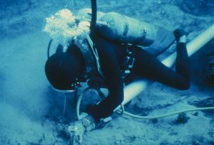Diver using an airlift to remove sediment.